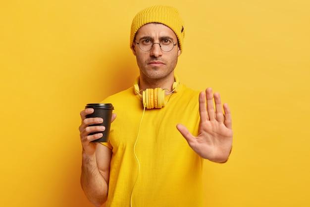 深刻な不満の男は、ジェスチャーを停止し、何かをすることを拒否し、ノーと言い、テイクアウトのコーヒーカップを持ち、眼鏡、黄色のカジュアルな服を着ます