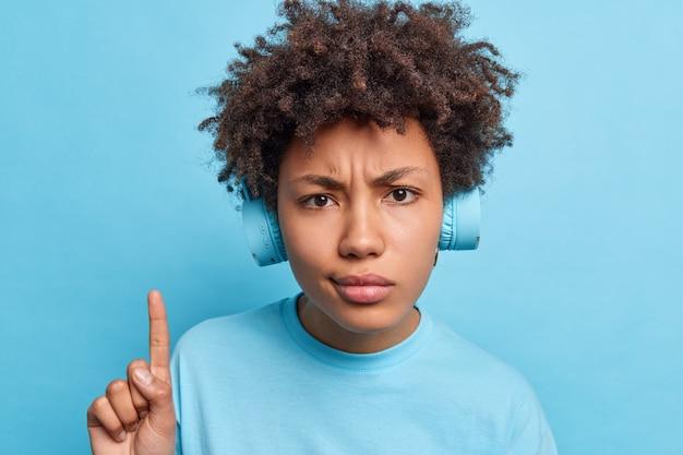 아프로 헤어 포인트 검지 손가락을 가진 심각한 불만족 혼혈 젊은 여성은 소음 제거를 위해 헤드폰을 사용하여 실내에서 자연스럽게 포즈를 취하는 시끄러운 이웃에 대해 불평합니다.