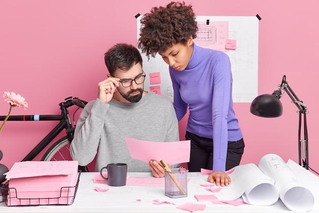 真面目な多様な建築家が、オフィスビルの計画のアイデアについて話し合い、紙やスレットを使ってデスクトップで青写真のポーズを作成します。人々のチームワークコラボレーションの概念