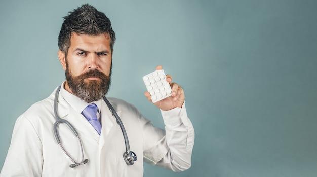 聴診器を備えた白い医療用ガウンの真面目な医者は、薬局と薬を手に持っています