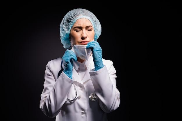 검은 색 배경에 고립 된 야간 근무 후 심각한 의사 아가씨