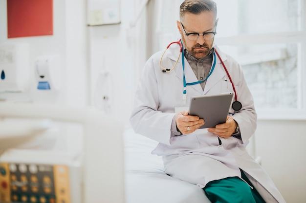 Серьезный доктор, читающий с планшета