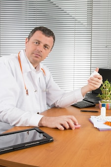 Serious doctor sitting at desk