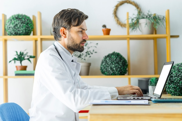 Serious doctor using laptop in office