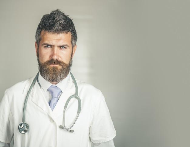 심각한 얼굴 준비가 된 외과 유니폼 의사의 클리닉에서 청진기를 가진 진지한 의사
