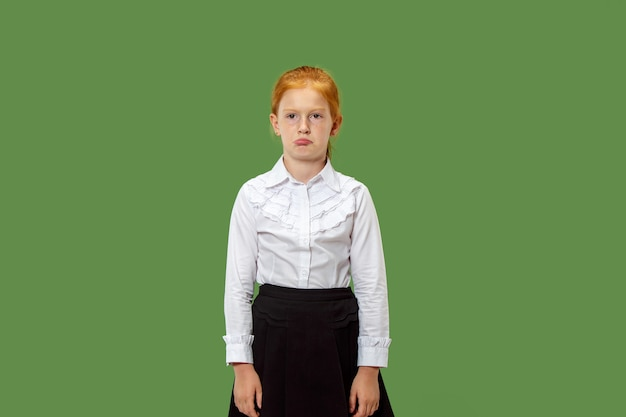 Serious doubtful, thoughtful, bored teen girl remembering something. young emotional woman. human emotions, facial expression concept. studio. isolated on trendy green. front