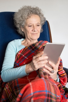 Serious elderly lady wrapped into blanket using tablet