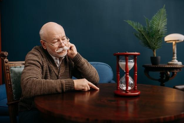 Серьезный пожилой мужчина смотрит на песочные часы в домашнем офисе, время не повернуть вспять