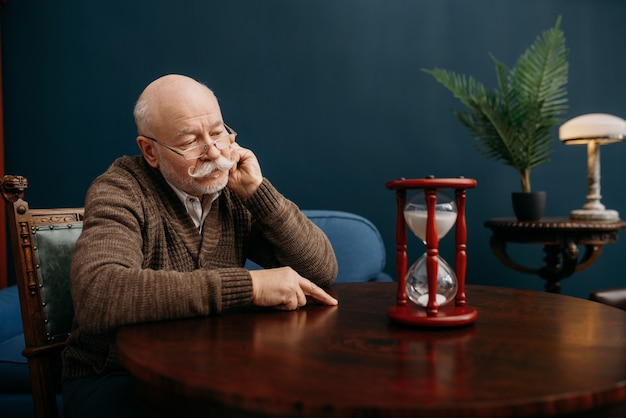 Serious elderly man looking on sandglass in home office, time cannot be turned back