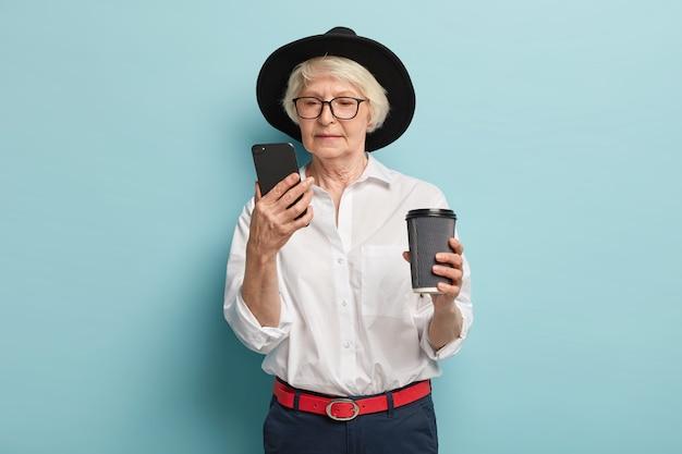 Серьезная пожилая женщина, сосредоточенная на смартфоне, ищет информацию в интернете, читает статьи в интернете, пьет кофе с собой, использует простое приложение для пенсионера, носит стильную одежду, позирует в помещении