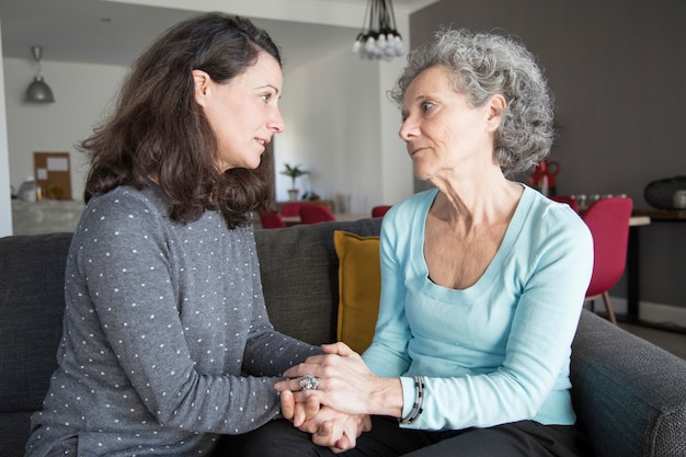 Serious elderly woman and her daughter talking and holding hands
