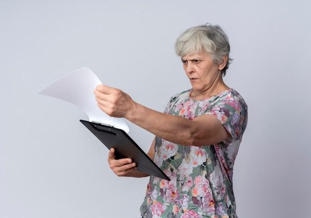 Серьезная пожилая женщина держит и смотрит в буфер обмена, изолированные на белой стене