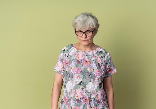 La donna anziana seria in vetri ottici sembra isolata sulla parete verde oliva