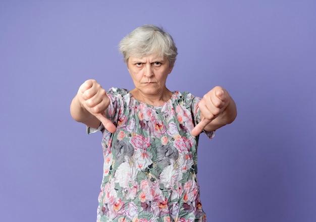 Серьезная пожилая женщина показывает палец вниз двумя руками, изолированными на фиолетовой стене