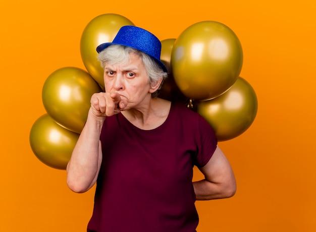 パーティーハットを身に着けている深刻な年配の女性は、後ろにヘリウム気球を保持し、コピースペースでオレンジ色の壁に隔離されたポイント