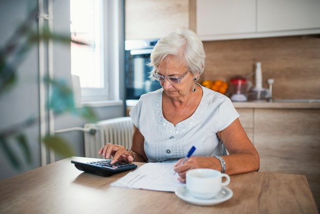 Serious elderly woman with calculator sitting at table