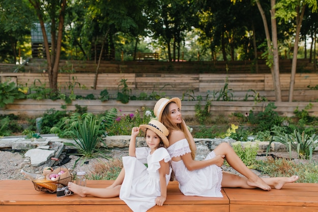 Serious elegant lady in white dress sitting on bench, touching her leg, after walk with daughter. outdoor portrait of romantic young mom and little girl in hat posing together with park.