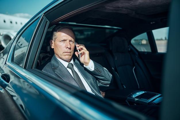 Серьезный элегантный мужчина едет на машине с водителем после приземления самолета и звонка