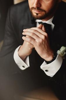 Серьезный элегантный мужчина укрепляет и держит скрещенными руками.