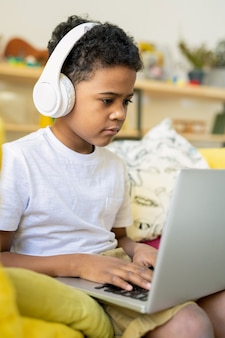 Серьезный школьник африканской национальности с наушниками печатает на ноутбуке, слушая дома образовательный онлайн-курс