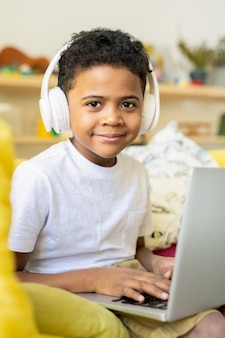 집에서 교육 온라인 과정을 듣는 동안 노트북에 입력하는 헤드폰으로 아프리카 민족의 심각한 초등학교 남학생