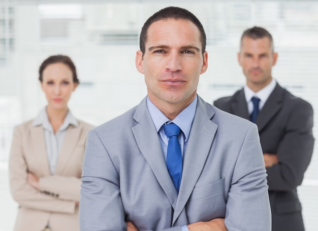 Serious employee posing with his colleagues on background
