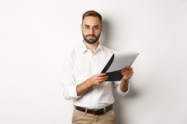 Grave datore di lavoro che guarda l'obbiettivo durante la lettura di documenti negli appunti, avendo colloquio di lavoro, in piedi