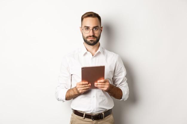 Grave datore di lavoro che lavora con tavoletta digitale, lettura con gli occhiali, in piedi