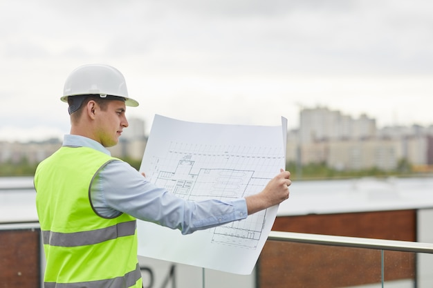 Serious engineer in work helmet examining the blueprint of new building while standing outdoors
