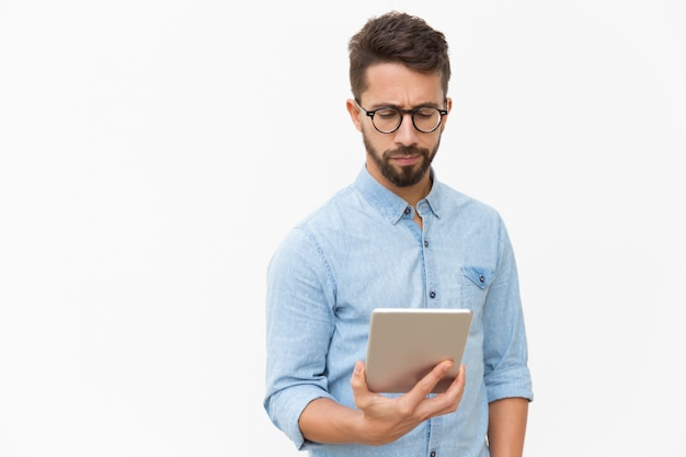 Serious entrepreneur checking email on tablet