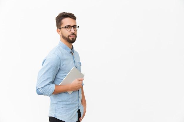 Serious entrepreneur in eyeglasses with tablet looking