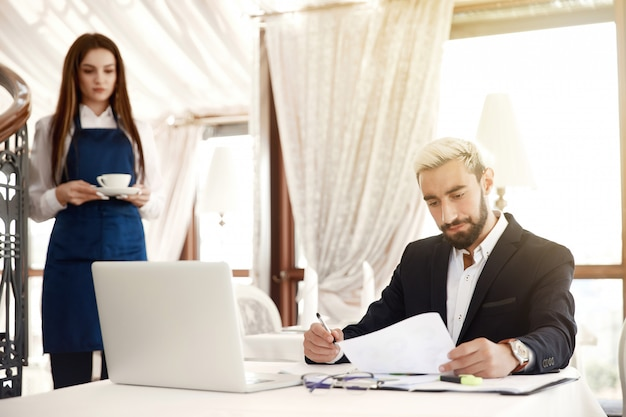 Serious entrepreneur is scanning thefinancial reviews  and the waitress is bringing him hot drink