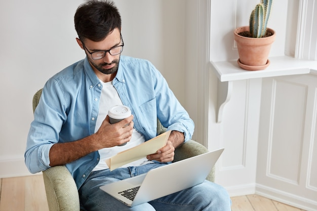 Serious entrepreneur takes care of business, works at home, concentrated into documents, has laptop computer on knees, holds takeaway coffee, sits in comfortable armchair.