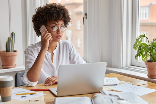 Serious ethnic female ceo wears round spectacles, tries to reach decision with colleague via cell phone