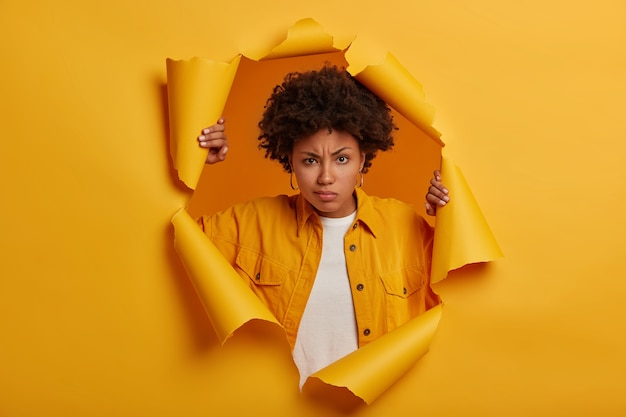 Serious ethnic woman frowns from displeasure, raises eyebrows, dissatisfied with something, wears fashionable denim jacket, stands in paper hole, being distressed and frustrated.