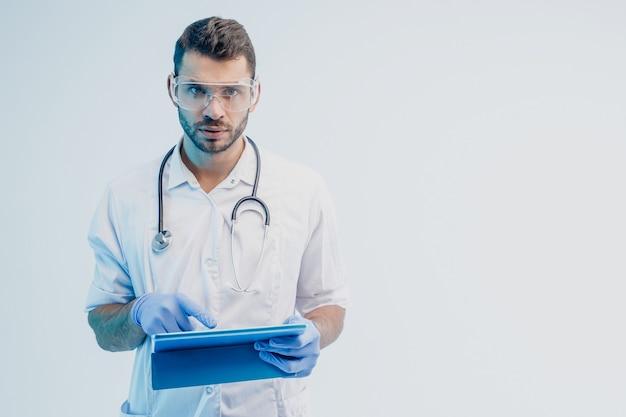Серьезный европейский мужчина-врач с цифровым планшетом. молодой бородатый мужчина со стетоскопом в белом халате, очках и латексных перчатках. серый фон с бирюзовым светом. студийная съемка. скопируйте пространство.