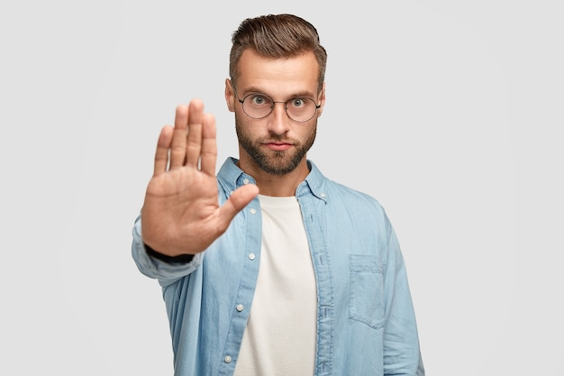 Un maschio europeo serio mostra un gesto di arresto, richiede qualcosa, ha un'espressione facciale rigorosa, indossa occhiali rotondi e camicia formale, isolato su un muro bianco. persone e concetto di linguaggio del corpo