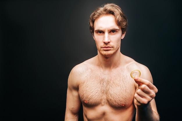 손에 콘돔을 보여주는 심각한 유럽 남자