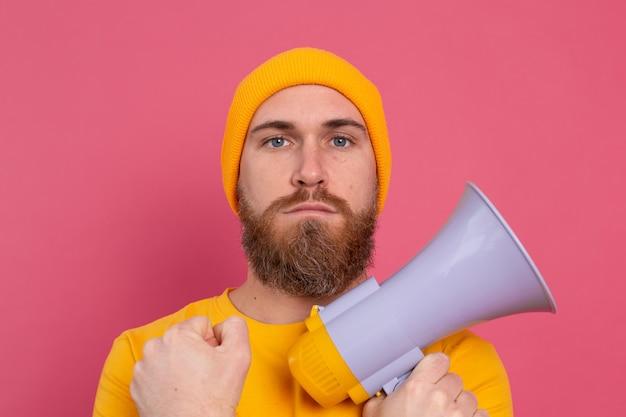 Uomo europeo serio con il megafono su sfondo rosa
