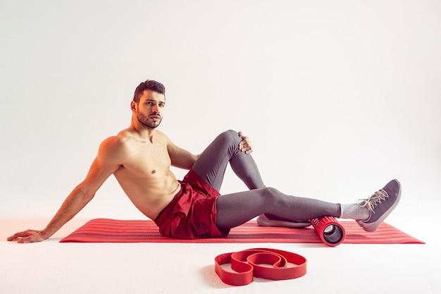 Серьезный европейский спортсмен сидит на фитнес-коврике с массажным роликом. молодой красивый бородатый мужчина с обнаженным спортивным торсом и глядя в камеру. изолированные на бежевом фоне. студийная съемка. копировать пространство