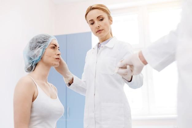 メスを取り、患者の近くに立って美容整形手術を行う真面目な経験豊富な女性外科医