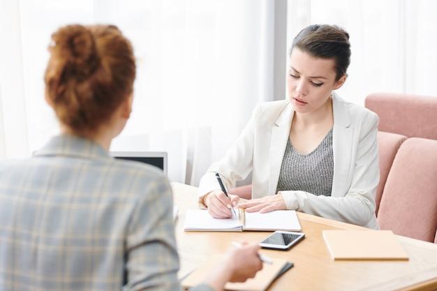 Серьезный опытный рекрутер леди сидит за столом и делает заметки во время собеседования с кандидатом на работу в кафе