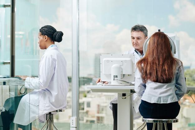젊은 여성의 시력을 검사하는 심각한 경험이 풍부한 안과 의사, 컴퓨터에서 그의 여성 동료 workng