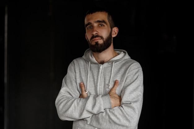 真面目な顔。黒い壁に立っている灰色のスウェットシャツのひげを持つハンサムなビジネスの若い男
