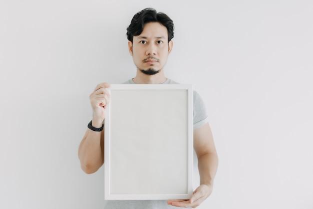 白い背景で隔離の空のフレームを保持している深刻な顔の男