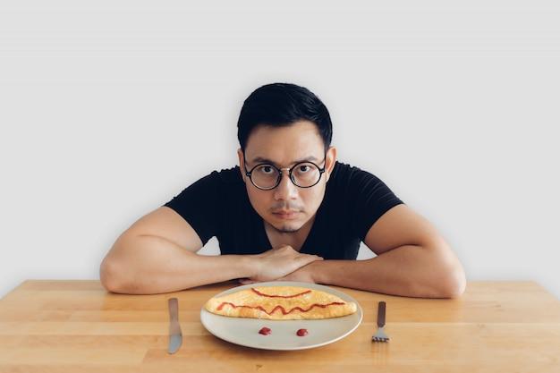 아시아 남자의 심각한 얼굴은 오믈렛의 집에서 만든 아침 식사 세트를 먹고있다.