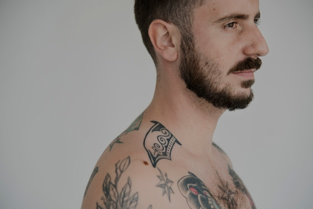 Serious facial expression naked tattooed man