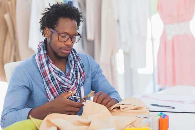 Serious fashion designer cutting textile