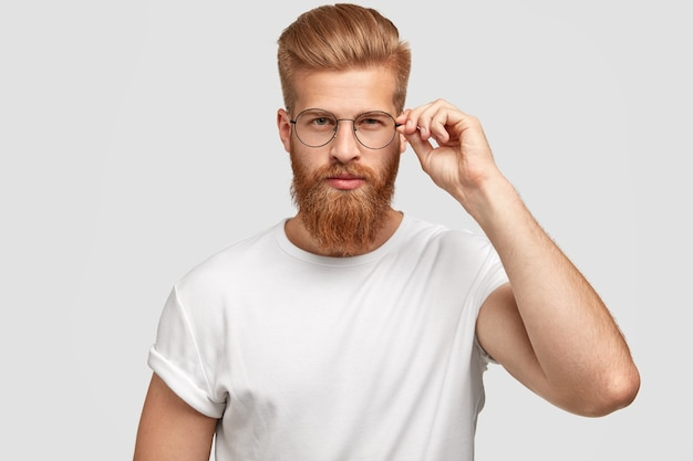 Serious fashionable man boss with thick ginger beard and hairdo, touches rim of spectacles