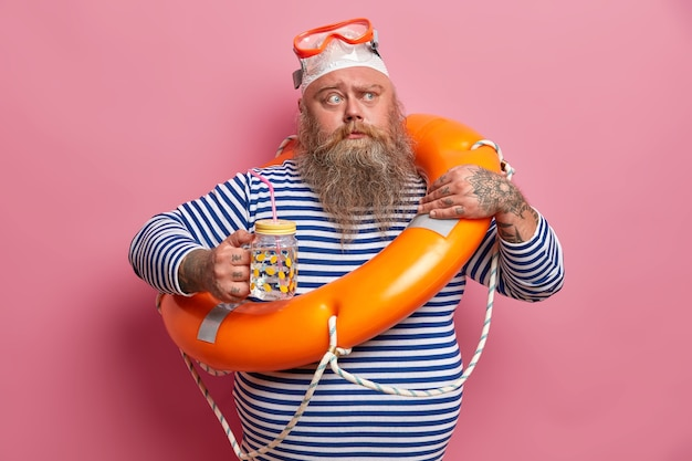 Serious fat man frowns eyesbrows, holds glass bottle of water, feels thirsty during hot day, wears striped sailor sweater, swimming goggles, poses with inflated lifebuoy for safe swim. safety holiday